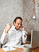 Mature businessman using phone in office, clenching fist, smiling