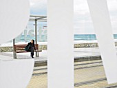 Woman waiting at tram stop viewed through some large lettering on glass shelter. Alicante, Spain.