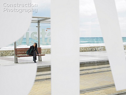 Woman waiting at tram stop viewed through some large lettering on glass shelter Alicante Spain