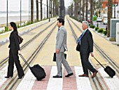 Businesswoman and two businessmen crossing double tram lines with suitcases at zebra crossing. Alicante, Spain.