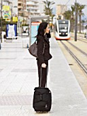 Side view of woman waiting at tram stop with tram in background. Alicante, Spain.