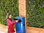 Young girl (5-7) putting can in public bin, Alicante, Spain,