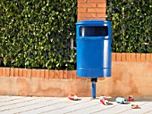 Public bin on pavement surrounded by discarded cans, Alicante, Spain,