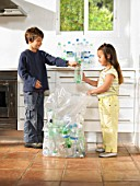 Boy (6-8) and girl (4-6) recycling bottles in kitchen