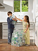 Young boy  (6-8) and girl 4-6) sharing recycling duties in  kitchen