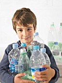 Young boy (6-8) holding an armful of recyclable plastic bottles, portrait
