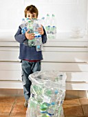 Young boy holding an armful of recyclable plastic bottles, portrait