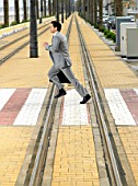 Man in suit with briefcase running across tram line crossing. Alicante, Spain.