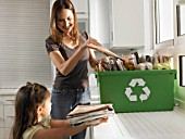 Mother and daughter (4-6)  sharing recycling duties in domestic kitchen