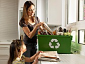 Mother and daughter (4-6) filling recycling box, smiling