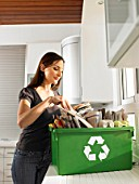 Woman putting newspapers in recycling box
