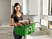 Woman holding recycling box, smiling, portrait