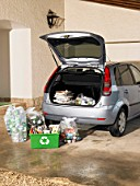 Box and bags of recycling on driveway by car