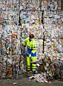 Man shoveling in front of a wall of recycling.
