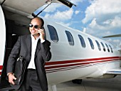 Smiling businessman exiting private jet on phone.