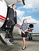 Businessman exiting private jet beside stewardess.