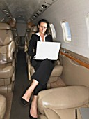 Businesswoman working on a laptop on a private jet.