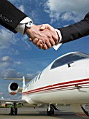 Two people shaking hands in front of private jet.