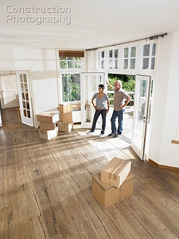 Couple moving boxes into empty house