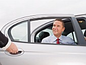 Chauffeur Holding Car Door Open for Smiling Businessman.