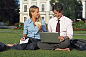 Businessman and businesswoman sitting in park working.