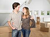 Couple moving into new home smiling.