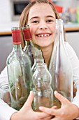 Girl recycling empty bottles