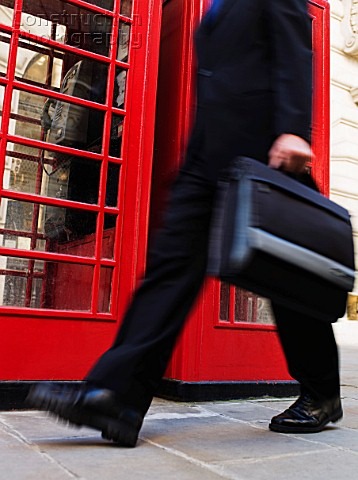 Businessman walking past phone booth