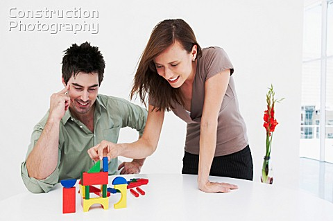 Man and woman happily build model house
