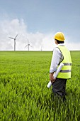 Man holding plans on a wind farm