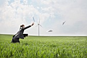 Businessman chasing papers on wind farm