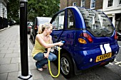 Young woman charging electric car