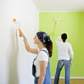 Man and woman painting a room