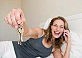 A female holding her keys on her bed.