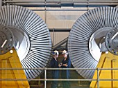 Engineers In Front Of Turbines