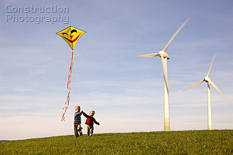 Two Boys Flying Kite at Wind Turbines