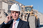 businessman with cell phone in quarry