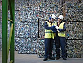 Recycle Workers With Bales Of Tin Cans