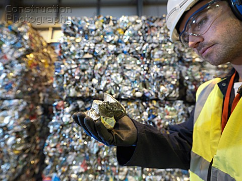 Worker In Recycle Plant Holding Can