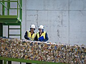 Workers Inspecting Bales Of Tin Cans