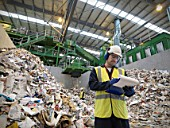 Worker With Notes In Recycle Plant
