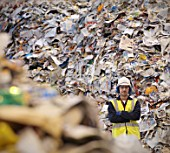 Worker With Paper In Recycle Plant