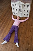A girl lying in front of her dollhouse.