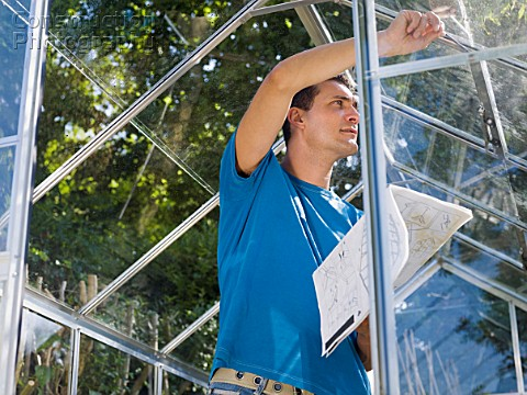 Man building greenhouse in garden