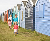 Children running past beach huts