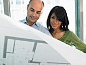 Man and woman looking at blue prints