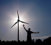 man raising arms at sun and Wind Turbine