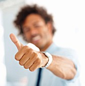 Executives hand showing thumbs up sign