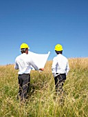 contractors with blueprints in field