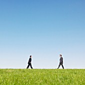 businessmen walking in field
